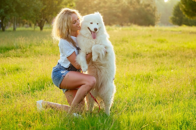 Bella e affascinante donna bionda sorridente a trentadue denti in pantaloncini di jeans sono seduti al vetro che abbraccia il cane samoiedo sveglio lanuginoso bianco sullo sfondo del campo di raggi del tramonto del parco estivo. animale domestico e padrona.