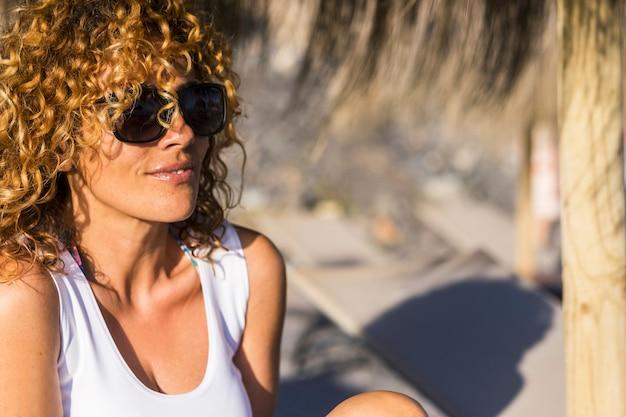 Bella donna bionda attraente allegra che sorride nell'attività di svago all'aperto in una giornata di sole. concetto di vacanza. occhiali da sole e mezza età femminile sexy.