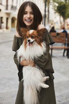 Bella e allegra ragazza modella bruna con sorriso splendente, in abito corto con un piccolo cane carino papillon sulle sue mani in posa all'aperto nel centro storico della città