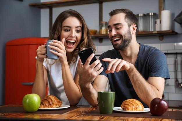 Bella coppia allegra facendo colazione in cucina, utilizzando il telefono cellulare