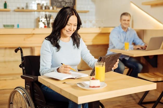 Bella donna allegra disabile che si siede su una sedia a rotelle e scrive sul suo taccuino e lavora sul suo tablet in un caffè e un uomo seduto in background