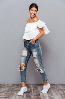 Bella ragazza bruna sorridente allegra in posa e guardando la parte anteriore isolata su un muro grigio