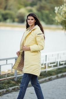 Bella donna allegra cammina lungo il vicolo in un cappotto autunnale.
