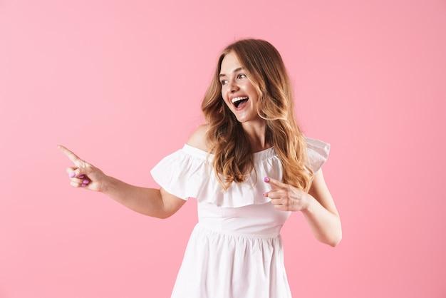Bella giovane ragazza bionda allegra che indossa un abito estivo in piedi isolato sul muro rosa, che punta lontano
