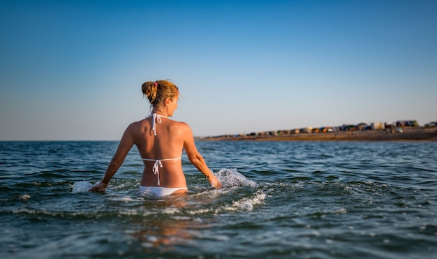La bella giovane donna allegra fa il bagno nell'acqua e si rallegra alzando le mani