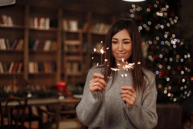 La bella giovane donna allegra osserva le luci brillanti del bengala stupefacente e il sorriso dell'albero di natale. la ragazza carina gode delle luci magiche nel nuovo anno. atmosfera positiva.