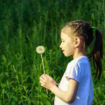 Bel bambino che soffia via fiore di tarassaco in primavera