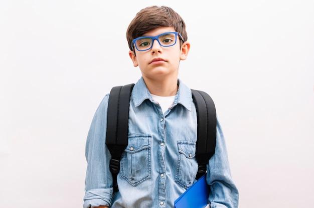 Bello studente del ragazzo del bambino con gli occhiali e lo zaino che tengono i libri su fondo bianco isolato