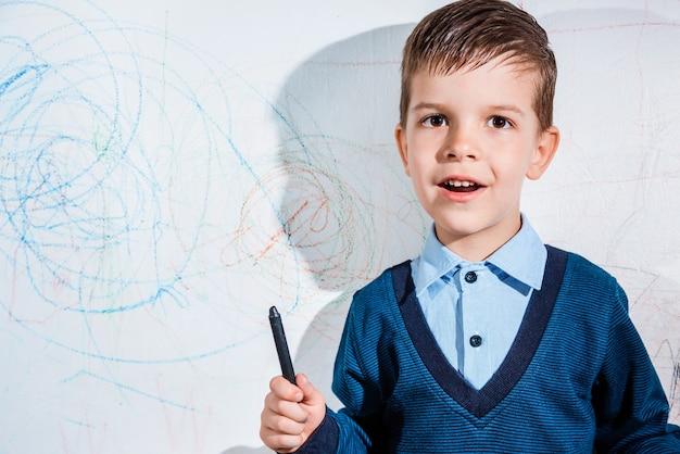 Bel bambino disegna sul muro con matite colorate