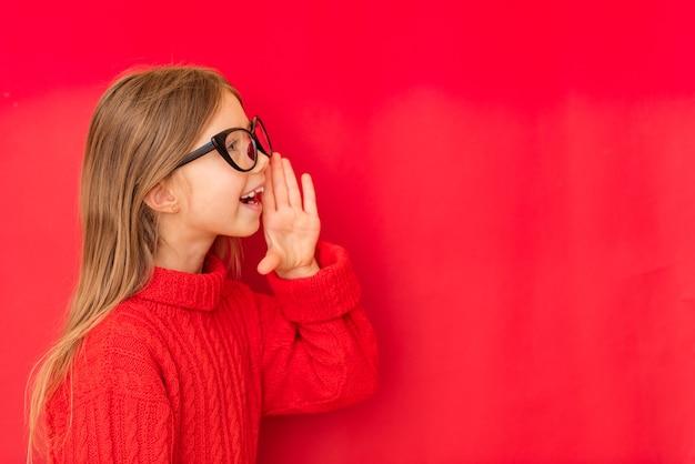 Bella ragazza bambino che grida, usando la bocca per dire qualcosa o chiamare qualcuno