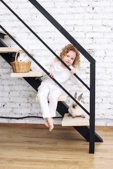 Bella bambina con i capelli ricci e con soffici conigli animali a casa in interni bianchi