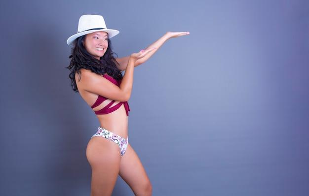 Bella donna cinese in bikini che indica qualcosa accanto a lei
