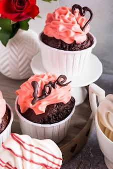Bellissimo cupcake al cioccolato, crema rosa, biscotti della meringa e rose rosse sulla superficie della pietra grigia. san valentino, festa della mamma, concetto di matrimonio