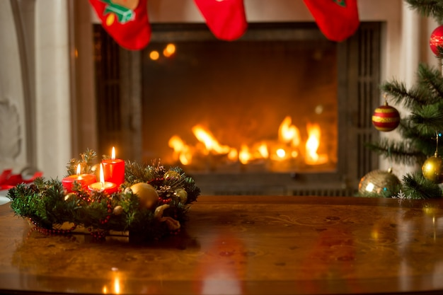 Bellissimo sfondo natalizio con candele accese sul tavolo di legno davanti al camino e all'albero di natale