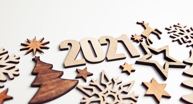 Il bellissimo sfondo natalizio con tante piccole decorazioni in legno e numeri in legno 2021 sulla scrivania bianca.