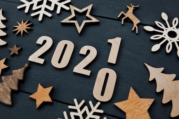 Il bellissimo sfondo natalizio con tante piccole decorazioni in legno e numeri in legno 2021 sulla scrivania in legno.