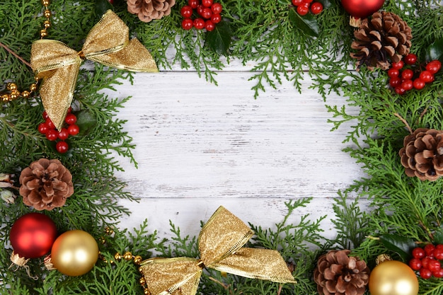 Bellissimo bordo natalizio di abete e vischio su fondo in legno