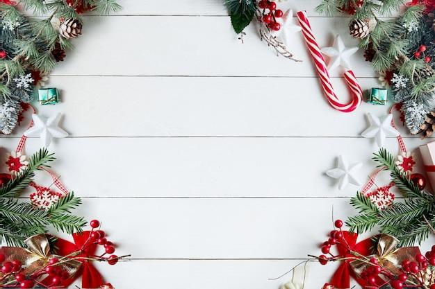 Bella composizione di natale su sfondo bianco con scatole regalo di natale, rami di abete innevato, coni di conifere, decorazioni natalizie, bastoncino di caramello e bacche rosse.