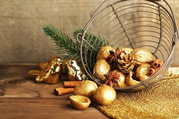 Bellissima composizione natalizia con noci dorate, su tavola di legno