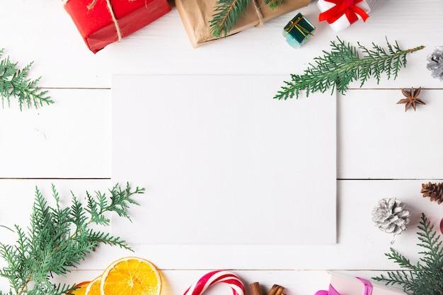Bella composizione di natale su fondo bianco in legno con scatole regalo di natale, frutta secca, decorazioni natalizie, bastoncino di caramello. nuovo anno.