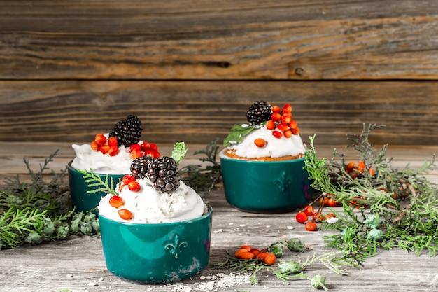 Bellissimo cupcake di natale con panna e frutti di bosco