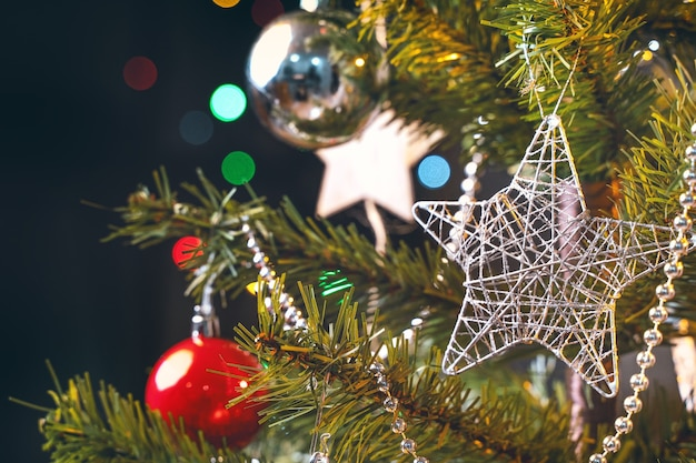 Bellissimo concetto di decorazione natalizia, pallina appesa all'albero di natale con punto luminoso scintillante, sfondo nero scuro sfocato, dettaglio macro, primo piano.