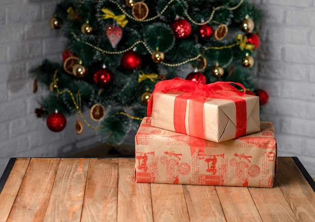 Bellissime scatole regalo di natale sul tavolo di legno accanto all'albero di natale nella stanza
