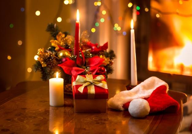 Bella foto di natale di candele accese con confezione regalo contro il camino