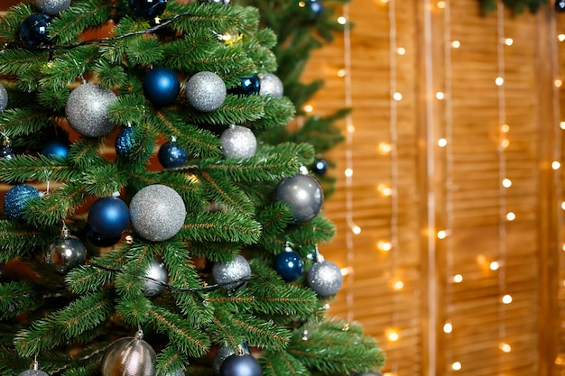 Bellissimo albero di natale decorato con giocattoli blu e argento. capodanno è presto. decorazioni per il giorno di natale