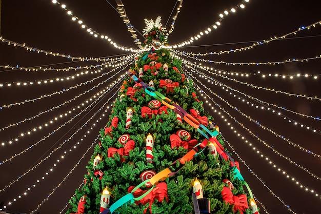 Bellissimo albero di natale decorato con luci natalizie. fiera serale.