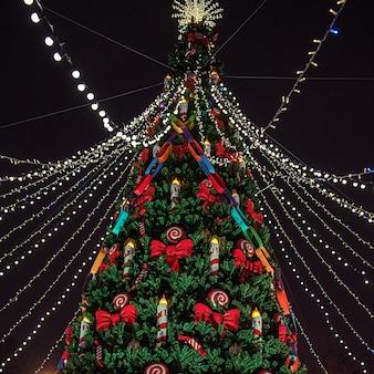 Bellissimo albero di natale decorato con luci di natale. fiera serale.