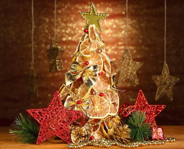 Bellissimo albero di natale di limoni secchi con decorazioni, su sfondo brillante