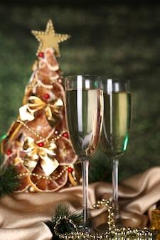 Bellissimo albero di natale e bicchieri di champagne su sfondo verde brillante