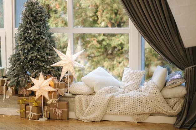 Bellissimo albero di natale con regali dalla grande finestra. l'inverno sta arrivando. plaid con cuscini