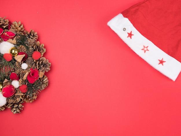 Bella ghirlanda di natale con cappello da babbo natale su sfondo rosso. decorazione interna festiva.
