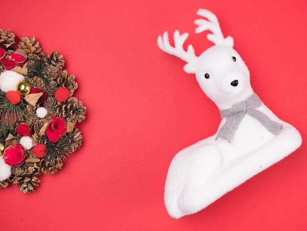 Bella ghirlanda di natale con giocattolo di renne bianche su sfondo rosso. decorazione d'interni festosa