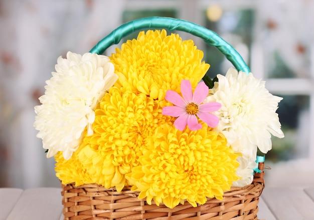Bella merce nel cestino del crisantemo sulla tavola di legno