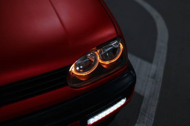 Bella macchina rossa classica con fari a led luminosi nella città notturna
