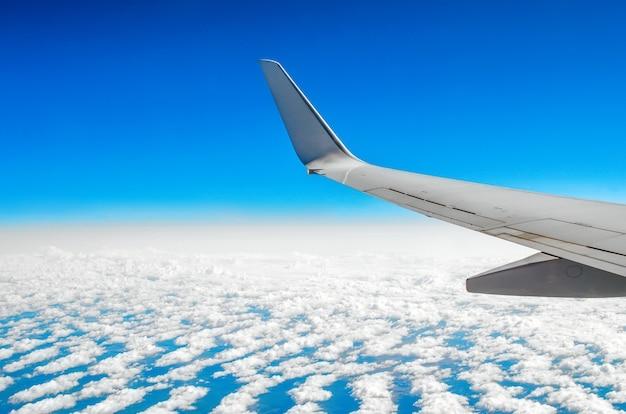 Bella vista classica dell'oblò durante un volo in aereo, nuvole di cielo blu e terra.