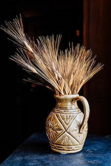 Bellissimo vaso di argilla con spighe di grano sul tavolo. fiori secchi e cereali per decorare gli interni.