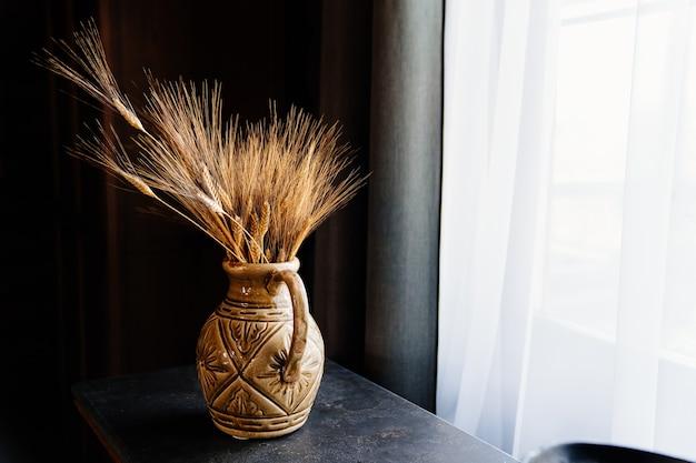Bellissimo vaso di argilla con spighe di grano sul tavolo