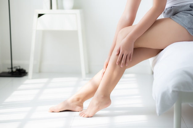Giovane donna asiatica del bello primo piano che si siede su un letto che segna le gambe con pelle liscia morbida nella camera da letto