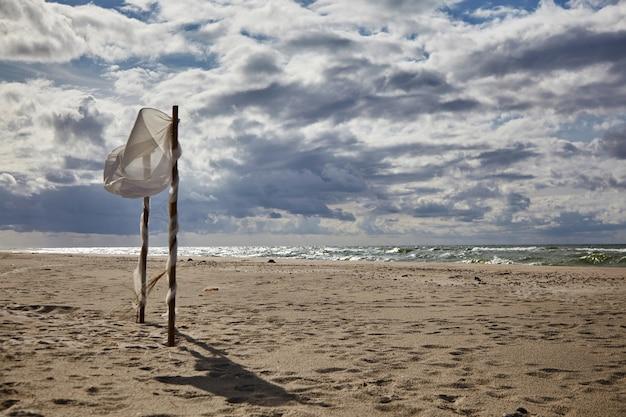 Belle nuvole e tenda da matrimonio strappata dal vento sulla spiaggia sabbiosa. matrimonio in spiaggia
