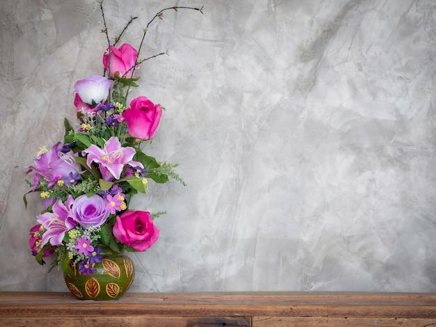 Bellissimi fiori bouquet colorati nella decorazione del vaso vintage su tavola di legno su sfondo di muro di cemento in stile loft con spazio di copia.