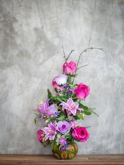 Bellissimi fiori colorati del mazzo nella decorazione del vaso dell'annata sulla tavola di legno sul muro di cemento in stile loft con lo spazio della copia, stile verticale.