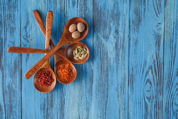 Belle spezie colorate in cucchiai su un vecchio tavolo di legno blu.