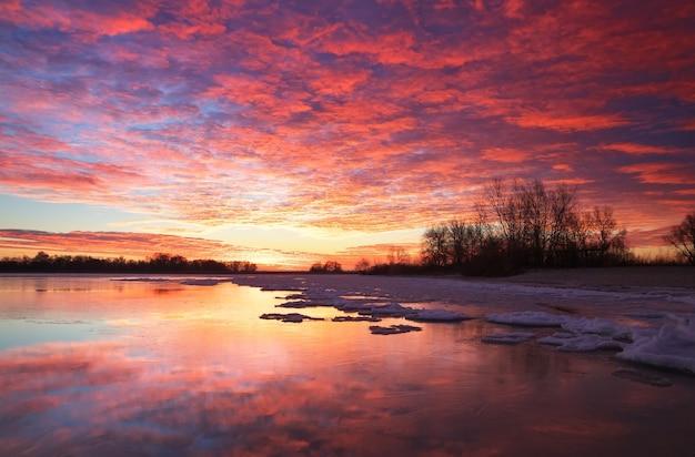 Bellissimo paesaggio invernale colorato con lago ghiacciato e cielo al tramonto. fenomeno meteorologico insolito