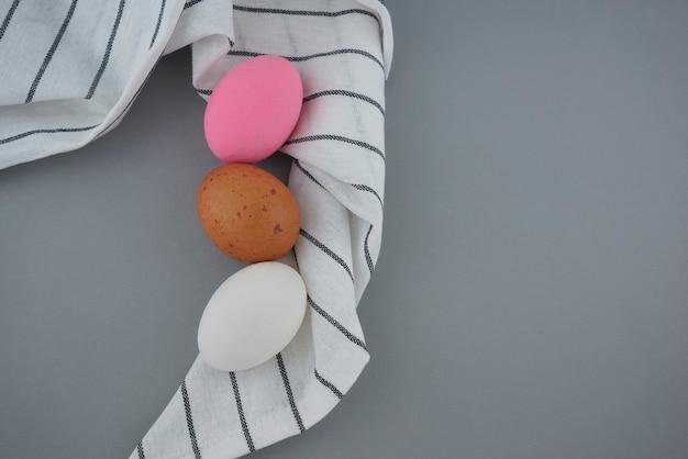 Bellissime uova colorate bianco marrone rosa still life food styling con motivo strofinaccio panno
