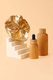 Bella composizione dalle bottiglie dei cosmetici e dal fiore di fenicottero dorato