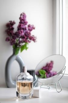 Bella composizione di profumo e fiori lilla. l'aroma fresco dei fiori pubblicizza